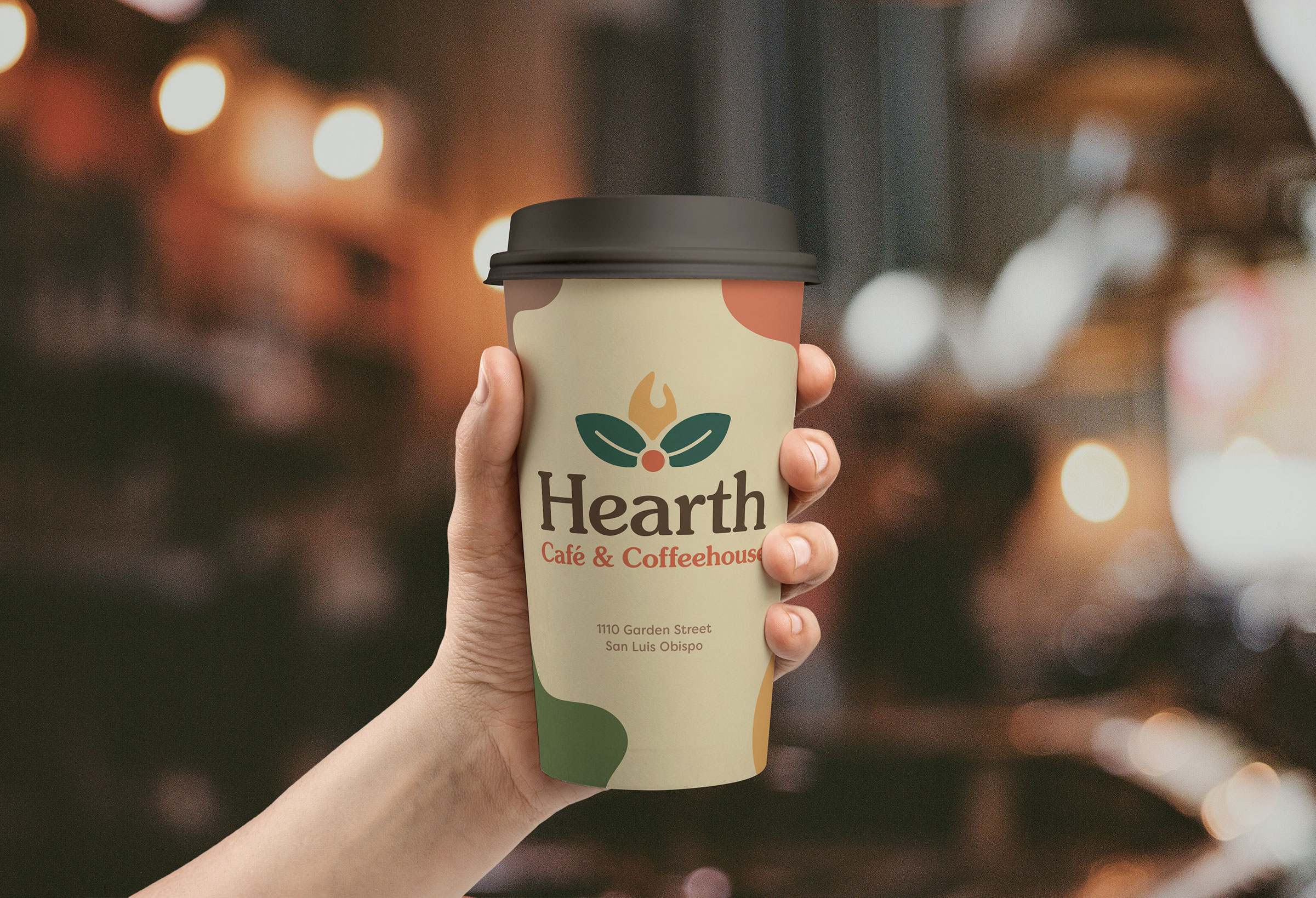 Hearth's rebranded to-go coffee cup, held in a hand against a soft background