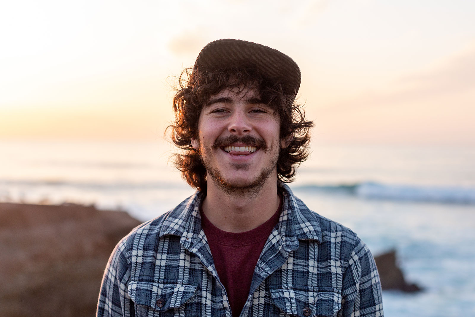 Close-up portrait of Cody wearing a hat and smiling against a blurry background of the coast at sunset