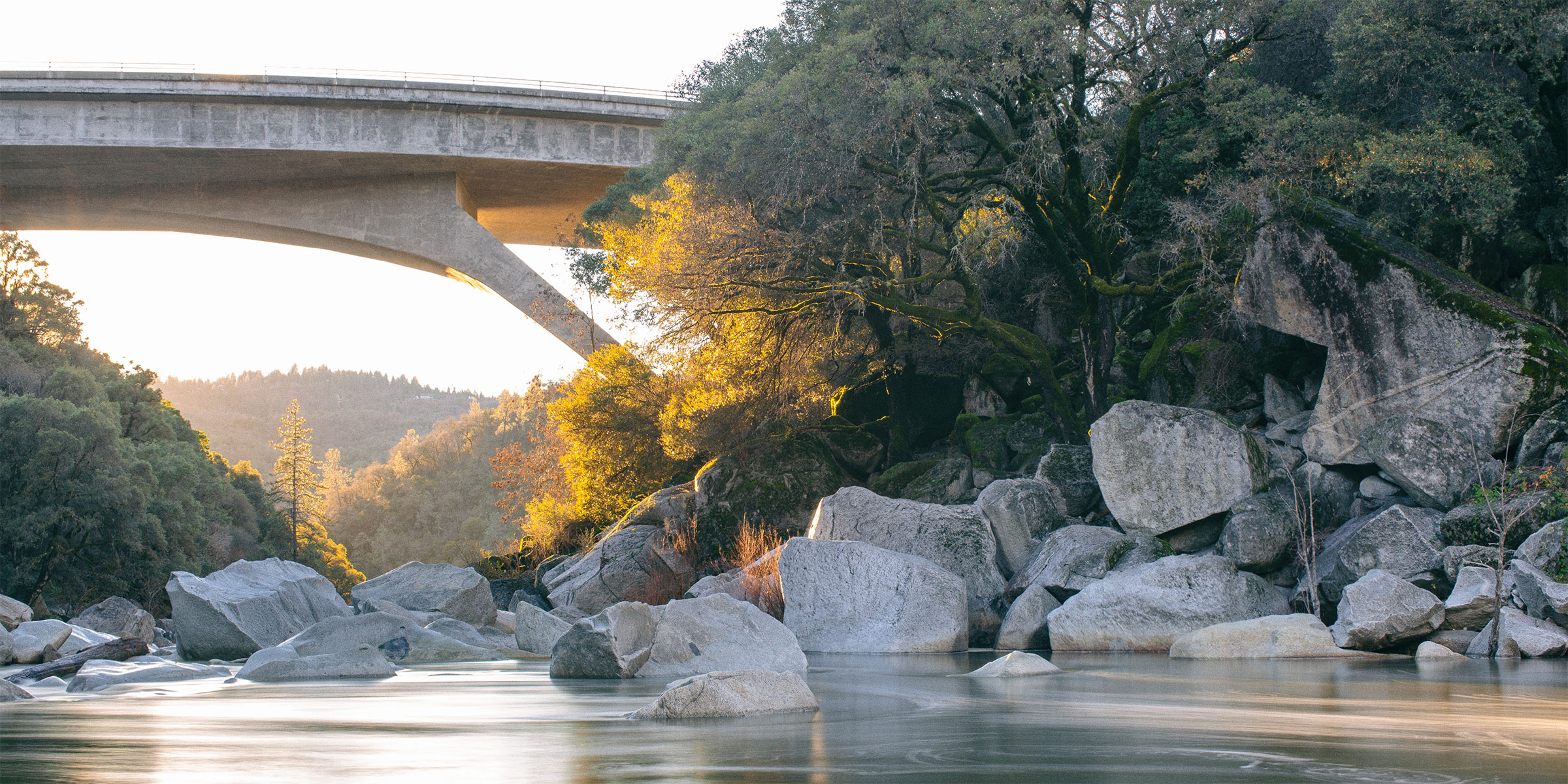 Long-exposure photo of the South Yuba River at golden hour, showing the water flowing around rocks and under a bridge, with trees on the right side bank